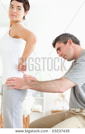 Chiropractor examining a brunette woman's back in a room