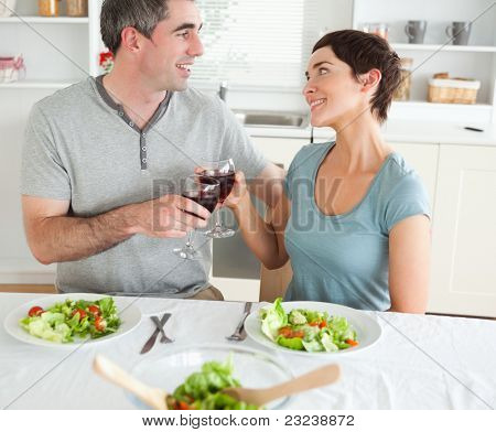 Close up of a cute couple toasting with redwine in a dining room