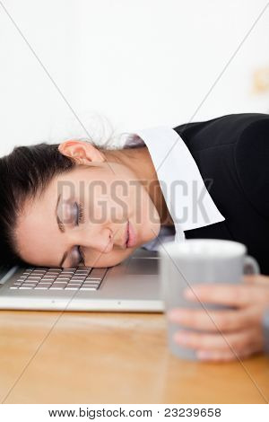 A businesswoman is sleeping with her head on laptop whilst holding a cup of coffee