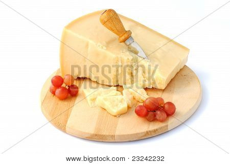 italian cheese on wooden cutting board with red grapes