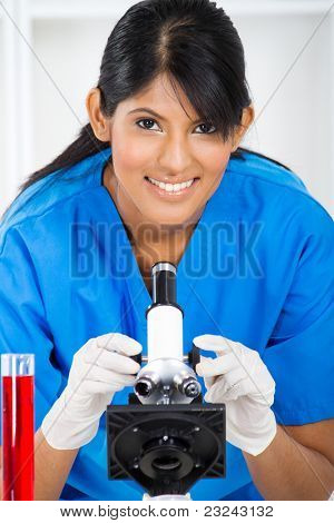 young lab technician using microscope