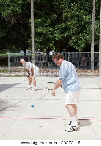 Father and adult son playing racquetball outdoors.
