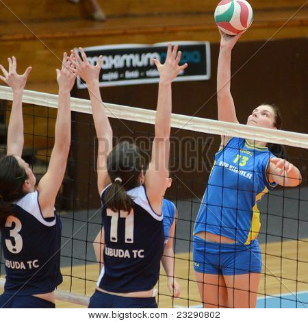 KAPOSVAR, HUNGARY - APRIL 24: Gabriella Kondor (13) strikes the ball at the Hungarian NB I. League woman volleyball game Kaposvar (blue) vs Ujbuda (black), April 24, 2011 in Kaposvar, Hungary.