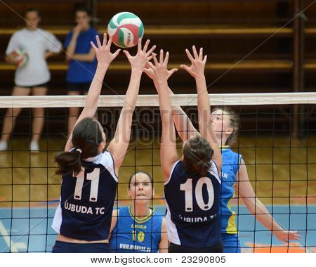 KAPOSVAR, HUNGARY - APRIL 24: Zsanett Pinter (R) strikes the ball at the Hungarian NB I. League woman volleyball game Kaposvar (blue) vs Ujbuda (black), April 24, 2011 in Kaposvar, Hungary.