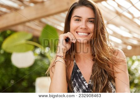 Brunette Smiling Female Sits In