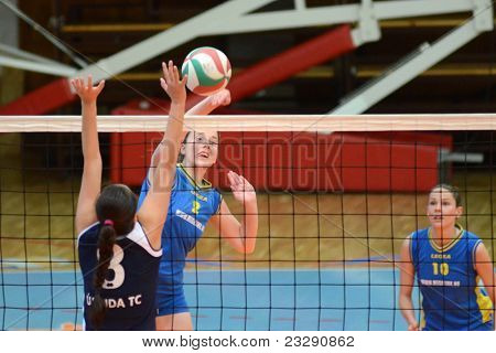 KAPOSVAR, HUNGARY - APRIL 24: Zsanett Pinter (2) strikes the ball at the Hungarian NB I. League woman volleyball game Kaposvar (blue) vs Ujbuda (black), April 24, 2011 in Kaposvar, Hungary.