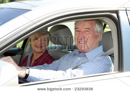 Senior citizen couple sitting in their car