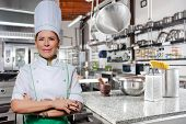 Portrait Of A Smiling Chef On A Kitchen Background. Looking Camera. Woman An Experienced Chef In A H poster