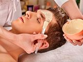 Mud facial mask of man in spa salon. Healing massage with clay full face. Beautician with bowl thera poster