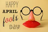a pair of fake eyeglasses, with nose and mouth, and the text happy april fools day, on a yellow back poster