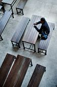 Teenage boy sitting alone in an empty canteen poster