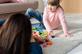 Daughter With Down Syndrome And Her Mother Playing With Toy Cubes poster