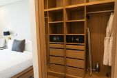 Large built-in wardrobe with shelves in bedroom where hanging bathrobes for guests of hotel. Honeymoon concept