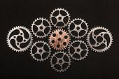 Rose-gold cogwheel surrounded by metal cogwheels on a black background. Individuality and uniqueness poster