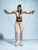Fitness Girl Performs Exercises With Resistance Band. Photo Of Fitness Model Workout On Grey Backgro poster