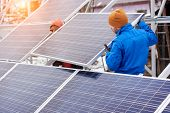 Technicians In Blue Suits Mounting Photovoltaic Solar Panels On Roof Of Modern House. Solar Modules  poster