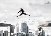 Business Woman Jumping Over Gap With Flying Paper Planes In Concrete Bridge As Symbol Of Overcoming  poster