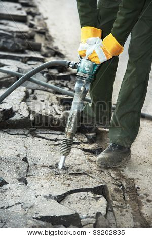 Road worker breaking street asphalt with jackhammer pneumatic paving breaker drill at repairing roadwork