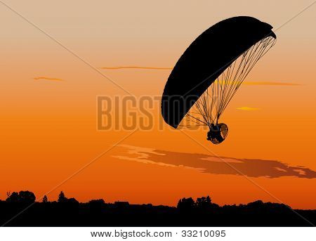 Silhouette of powered paraglide or paramotor against sunset sky
