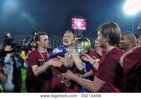 Soccer player celebrating the victory with the golden ball trophy