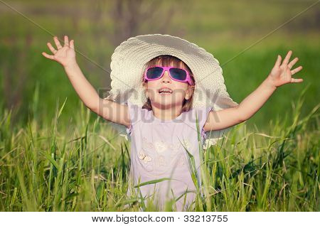 A beautiful little girl with a hat in a grain field