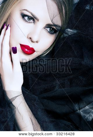 beautiful woman with red lips, smoky eyeshadow and purple manicure on the background of black veil with copy space.