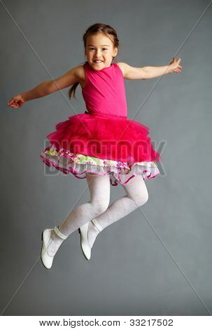 Full length portrait of a cute little girl in jump on grey background