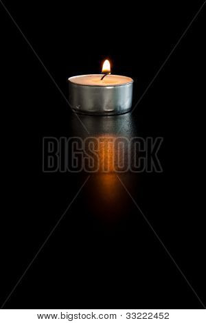 Lightened tea candle against a black background