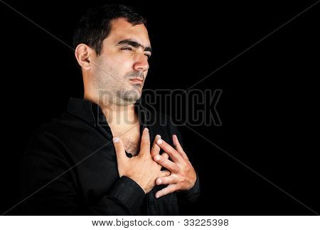 Side portrait of a young man feeling pain on his chest and touching it with his hands isolated on black