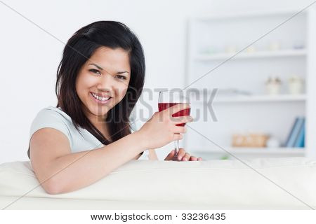 Woman holding a glass of red wine with one hand while resting her arm on a sofa in a living room