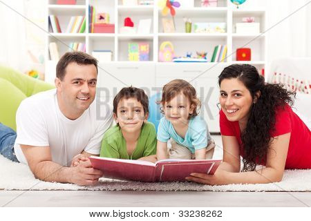 Young happy family with two kids reading a story book - laying on the floor