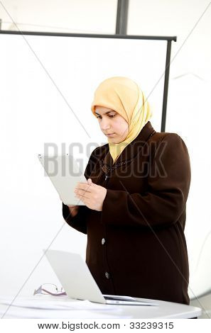 muslim Businesswoman standing on whiteboard,and holding a tablet
