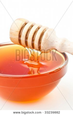Honey sticky trickle dropping in a honey bowl against a white background