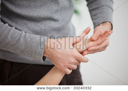 Masseur massaging the hand of  a woman in room
