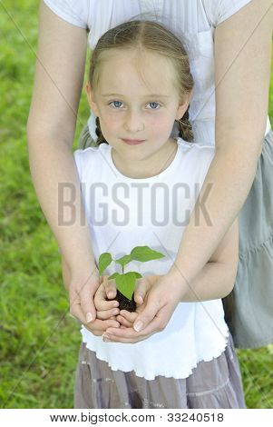 Girl with her mother holding a new plant