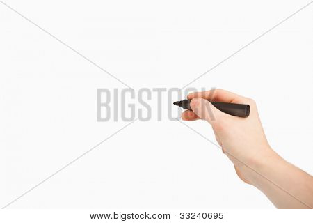 Fingers holding a black felt pen while pointing a blank space against a white background