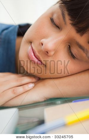 Close-up of a smiling student sleeping on her desk