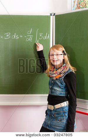Education - Child or pupil at blackboard in school in math