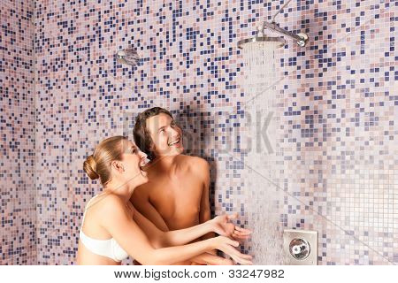 Young couple under experience shower doing wellness in Spa for cooling down after sauna