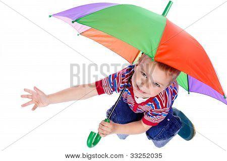 Little boy sitting under umbrella