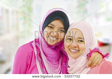 Happy Muslim women standing inside house