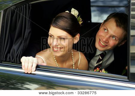 Smiling bride and groom looking out of widow of wedding car limousine.