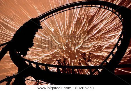 Silhouette of people on rollercoaster ride.