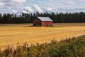 Lonely Red Barn In Field By The Road In The Finland In Fall poster