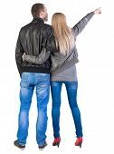 Back view of young couple pointing (woman and man). guy  and  girl  looking into the distance. Rear
