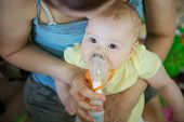 Baby Girl Making Inhalation With Nebulizer While Sitting On Moms Lap poster