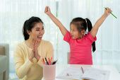 Happy Successful Asian Kindergarten Student And Her Mother Hands Raised Up To Celebrate The Successf poster