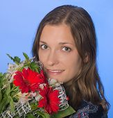 Young Happy Woman With Flowers On Blue Background