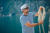 Portrait Of Senior Man Tying Knot And Securing A Mooring For His Hobby Yacht Sail Boat poster