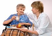 picture of health-care  - Health care worker and elderly woman in wheelchair needs help - JPG